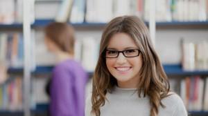 Студентка в очках в библиотеке